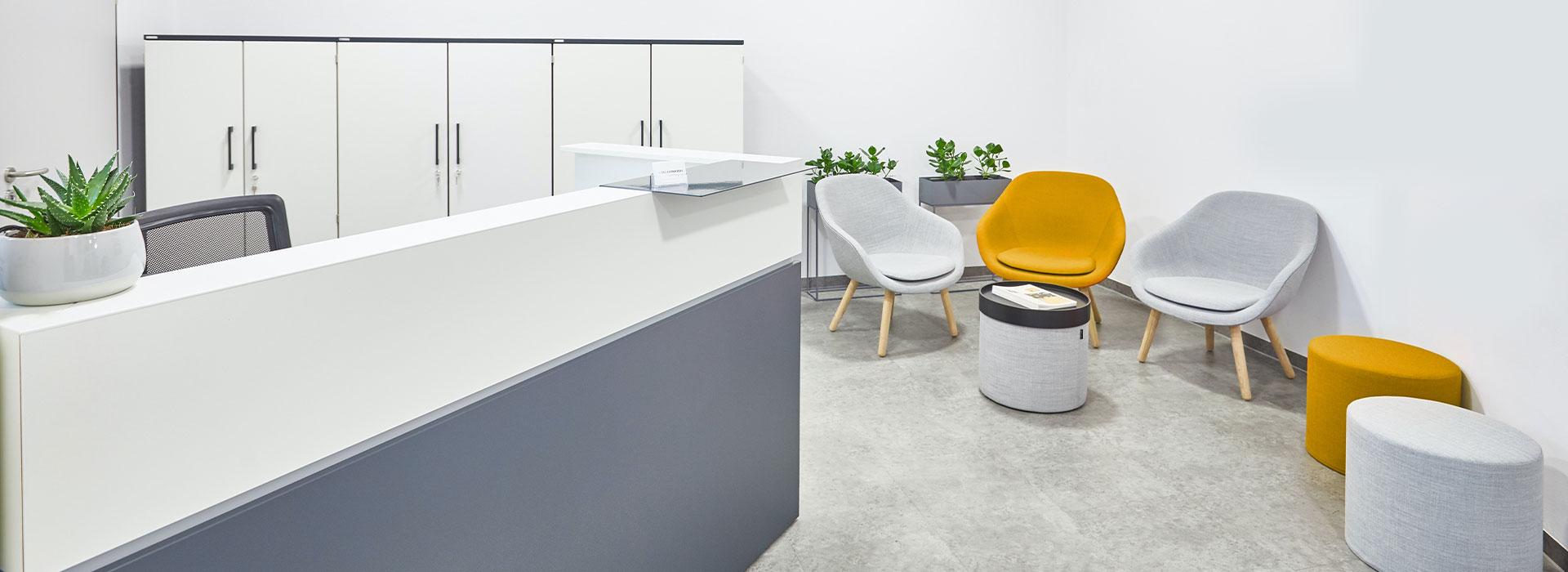Der Eingangsbereich der Physiopraxis mit drei Stühlen, zwei Hockern und einem Empfangstresen