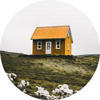 Ein orangenes Haus auf einer grüne Wiese.