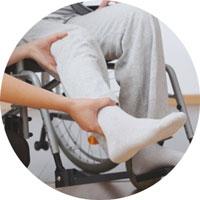 Der Patient sitzt im Rollstuhl und der Physiotherapeut hebt den Fuß.