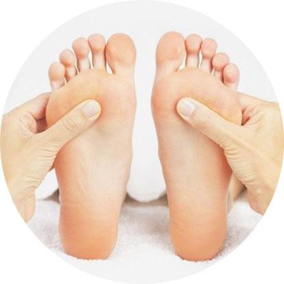 Zwei Füße werden von zwei Händen massiert.