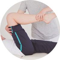 Der Physiotherapeut winkelt das Bein des Patienten an.