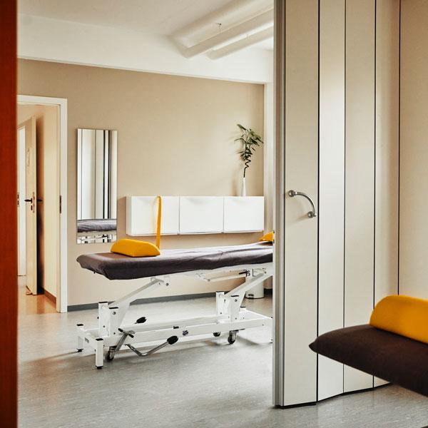 Zwei helle Behandlungsräume mit einer Trennwand